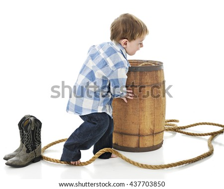 "An adorable 2-year-old ""cowboy"" pushing a rustic old barrel that's surrounded by a thick rope.  On a white background."