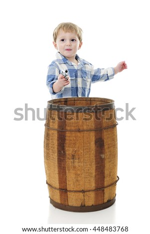 """An adorable 2-year-old """"cowboy"""" shooting his toy gun from behind an old barrel.  On a white background. - stock photo"""