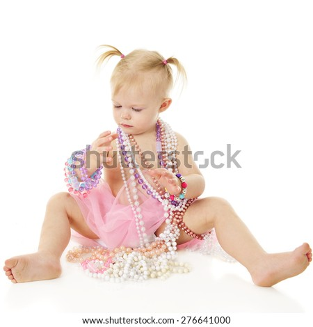 An adorable 2-year-old draped in beaded necklaces while looking at other twisted around her writs.  On a white background. - stock photo