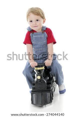 An adorable 2-year-old dressed as a train engineer, happily riding a toy train engine.  On a white background. - stock photo