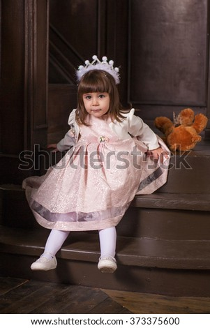 An adorable 2-year-old girl and her toy bear. Portrait Little Princess in full in the interior - stock photo