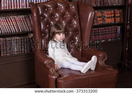 An adorable 2-year-old girl is sad. Little Princess sitting in a chair . Portrait in full growth in the interior - stock photo