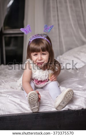 An adorable 2-year-old girl is sad. The little Princess sits in bed and cries - stock photo