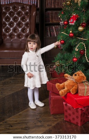 An adorable 2-year-old girl near Christmas tree with gifts at toy shows. Portrait in full growth in the interior - stock photo
