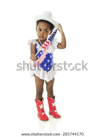 An adorable 2 year old in a star spangled majorette outfit adjusting her hat as she holds an American flag.  On a white background. - stock photo