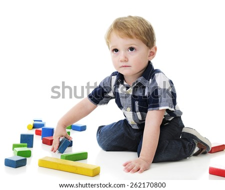 An adorable 2-year-old looking up as if to ask if it's okay for him to play with the colorful blocks surrounding him.  On a white background. - stock photo