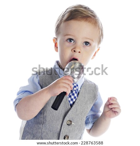 An adorable 2-year old singing (or talking) into a microphone.  On a white background. - stock photo