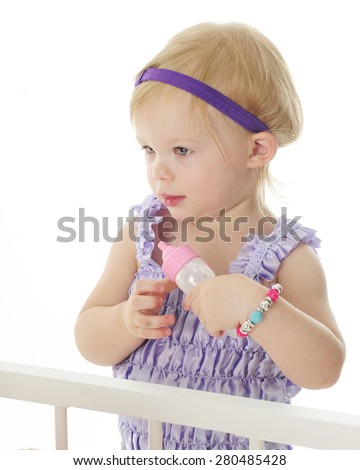 An adorable 2-year-old standing crib-side ready to feed her dolls with a baby bottle.  On a white background. - stock photo