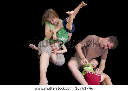 An adorable young family playing and having fun. Studio shot isolated on black.