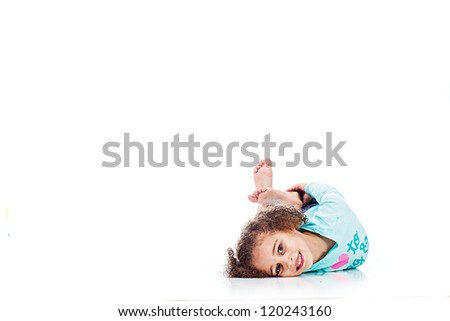 An adorable young girl laying down playfully - stock photo