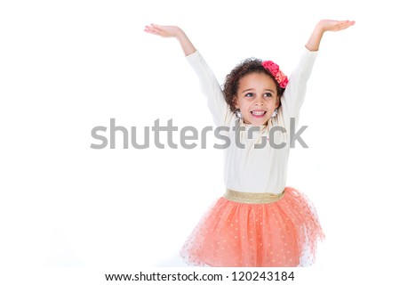 An adorable young girl with a bright smile lifting her arms in joy. - stock photo