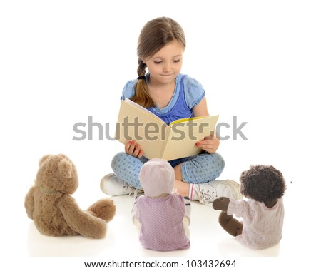 "An adorable young ""teacher"" reading a book to her toy students.  On a white background."