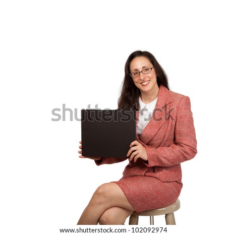 An adult businesswoman wearing a suite on a isolated white background holding a black board with room for copy