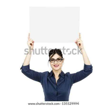 An adult (early 30's) black haired caucasian woman holding a blank sign over her head while looking at the camera with a large toothy smile. Isolated on white background. - stock photo