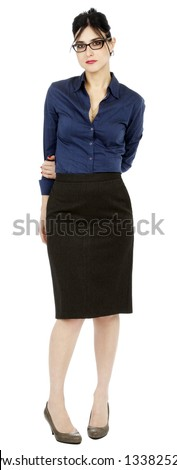 An adult (early 30's) black haired caucasian woman, wearing a blue buttoned shirt, a dark gray skirt  looking at the camera with a somewhat timid expression and posture. Isolated on white background. - stock photo