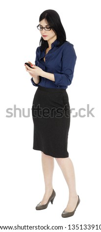 An adult early 30's black haired Caucasian woman, wearing a blue buttoned shirt and a dark gray skirt looking at a cellular phone - perhaps reading a message or dialing. Isolated on white background. - stock photo