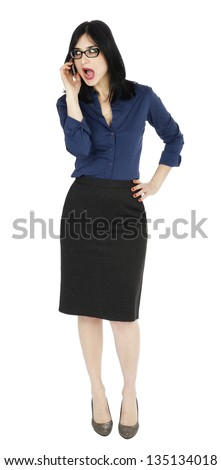 An adult (early 30's) black haired caucasian woman, wearing a blue buttoned shirt and a dark gray skirt; looking to the side while talking on the phone. Isolated on white background. - stock photo