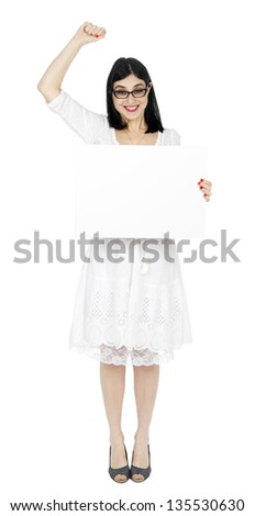 An adult (early 30's) woman holding a blank sign with her right hand, and her left hand raised in a success/winning gesture, while giving the camera a large toothy smile. Isolated on white background. - stock photo