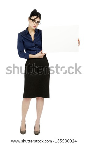 An adult (early 30's) woman wearing a blue buttoned shirt and a dark gray skirt, holding a blank sign next to her while looking at the camera serious expression. Isolated on white background.