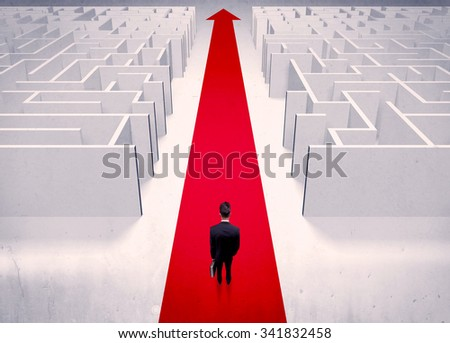 An adult elegant businessman standing on a red carpet arrow pointing ahead through a street with maze on two sides concept - stock photo