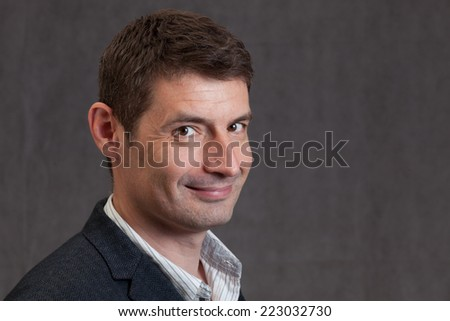 An adult male in his early forties wearing a jacket and shirt.  He is smiling with a cheeky look. - stock photo