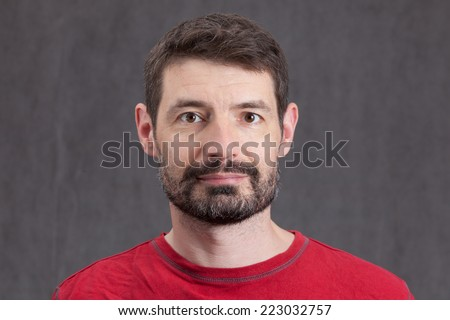 An adult male in his early forties with a full beard wearing a red tshirt.  He is smiling and looking directly at the camera.