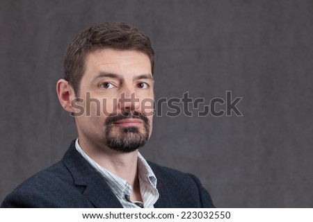 An adult male in his early forties with a goatee beard wearing a jacket and shirt.  He is looking serious. - stock photo