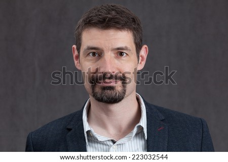 An adult male in his early forties with a goatee beard wearing a jacket and shirt.  He is smiling. - stock photo