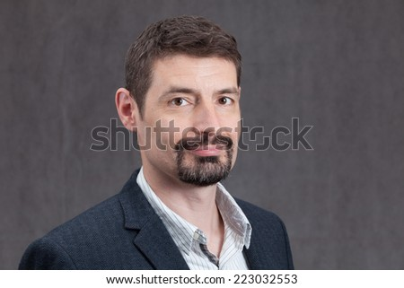 An adult male in his early forties with a goatee beard wearing a jacket and shirt.  He is smiling.