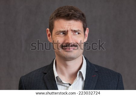 An adult male in his early forties with a 'movember' moustache wearing a jacket and shirt.  He is looking puzzled.