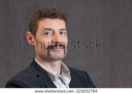 An adult male in his early forties with a 'movember' moustache wearing a jacket and shirt.  He is smiling.