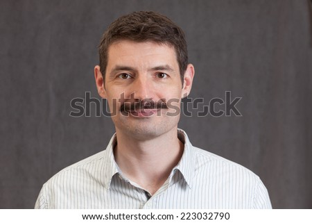An adult male in his early forties with a 'movember' moustache wearing a shirt.  He is smiling.