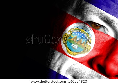 An adult sports fan with his face painted in the colors of Costa Rica's flag - stock photo