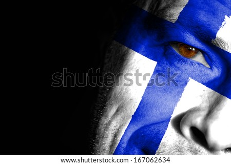 An adult sports fan with his face painted in the colors of Finland's flag - stock photo
