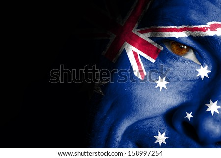 An adult sports fan with his face painted in the colors of the Australia's flag