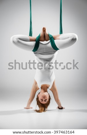 An adult woman practices different inversion - anti-gravity yoga positions in a bright well lit studio.  - stock photo