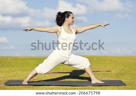 An adult woman standing on a black yoga mattress in the Virabhadrasana II (aka warrior II) pose, on a green lawn with cloudy blue sky in the background. - stock photo