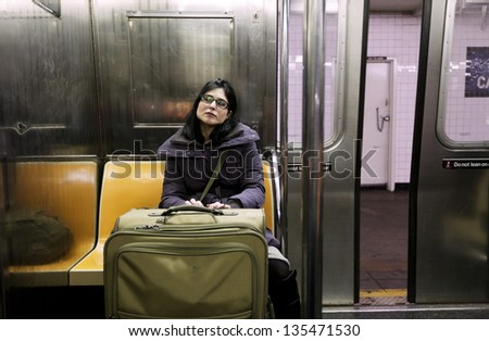 An adult woman with luggage sitting in the Brooklyn bound (downtown) A train subway in Manhattan, the door closing and train about to depart the station. - stock photo