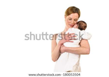 An adult woman with white shirt also has a white-clad sweet infant tenderly in her arms, isolated against a white background.