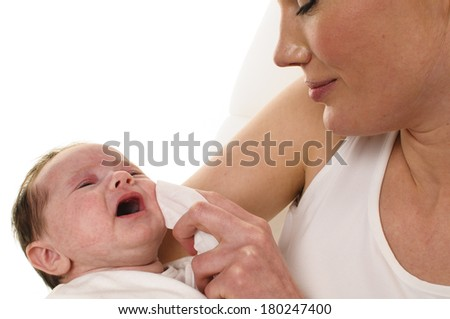 An adult woman with white shirt holding a also dressed in white infant tenderly in her arms and dabbed it with a tissue for cleaning the mouth, isolated against a white background. - stock photo