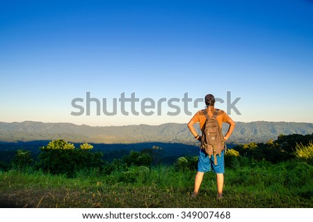 An adventurous traveler viewing top rocky mountain & valley during sunset time - stock photo
