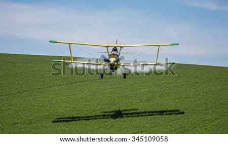 An aerial applicator/crop duster sprays a field of wheat to help maximize the productivity of the crop while eliminating invasive weeds and disease from the wheat crop. - stock photo