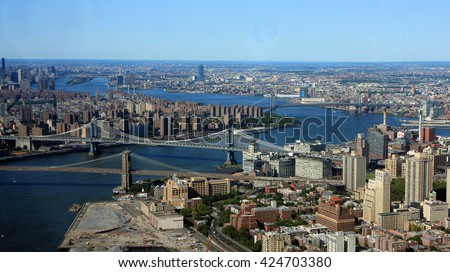 An aerial cityscape view of New York City with East River and Brooklyn, Manhattan, Williamsburg and Queensboro bridges visible - stock photo