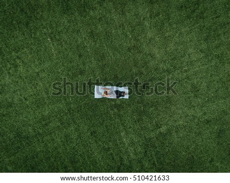 An aerial image of a woman doing yoga in a field of grass.