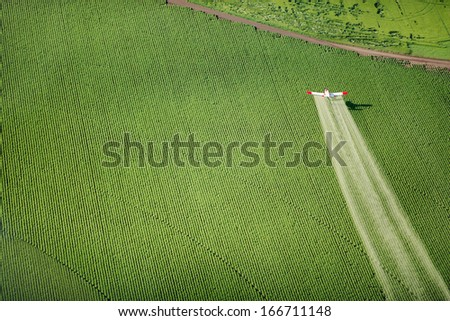 An aerial view of a crop duster as it flies low, spraying farm fields - stock photo