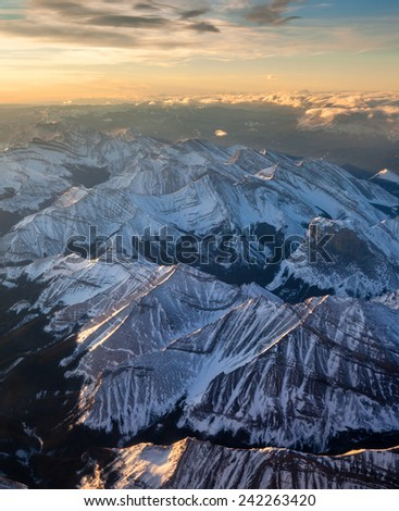 An aerial view of a golden sunrise at the break of dawn over the Canadian Rockies, with snow-capped mountains and clouds on mountain tops. - stock photo