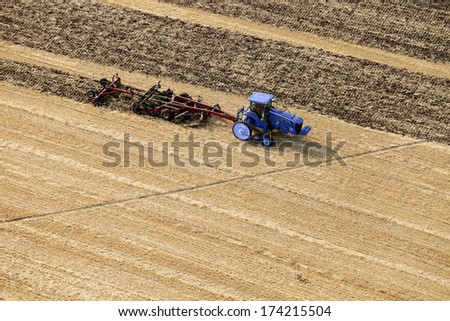 An aerial view of a tractor plowing farmland  - stock photo