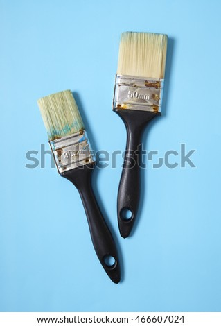 An aerial view of assorted decorators paint brushes on a bright blue background