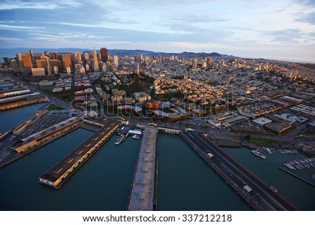 an aerial view of downtown san francisco with pier during sunset - stock photo