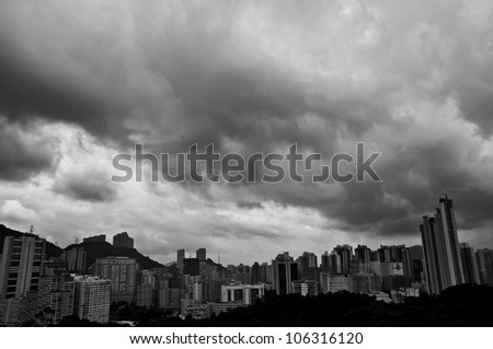 an aerial view of heavy clouds of a rainy day over the overpopulated Hong Kong city skyline - stock photo